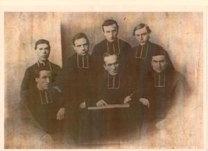 Il était malade, à quelques temps de finir sa vie sur terre. Les traits tirés, il accepte difficilement d'être photographié, mais pas seul : entourés de ses jeunes prêtres, et avec la croix.